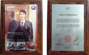 Подарочный диплом в честь годовщины журнала BMW;  справа — Благодарственное письмо от Объединённой металлургической компании